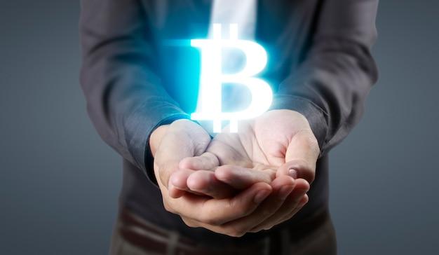 Ręce pokazujące ikonę bitcoina jako wirtualne pieniądze na cyfrowym nośniku
