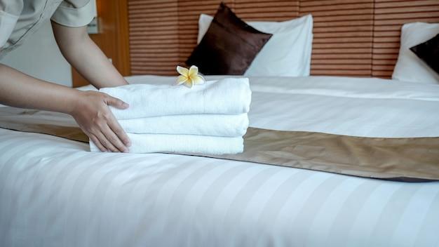 Ręce pokojówki kładącej kwiat plumeria i ręczniki na łóżku w luksusowym pokoju hotelowym