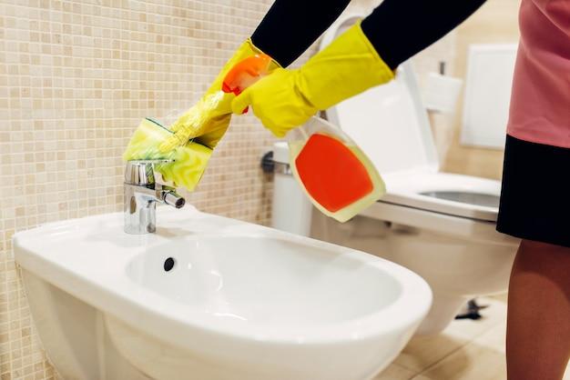Ręce pokojówki w gumowych rękawiczkach czyści bidet sprayem czyszczącym, wnętrze toalety hotelowej. profesjonalne usługi sprzątania, sprzątaczki, sanitariaty