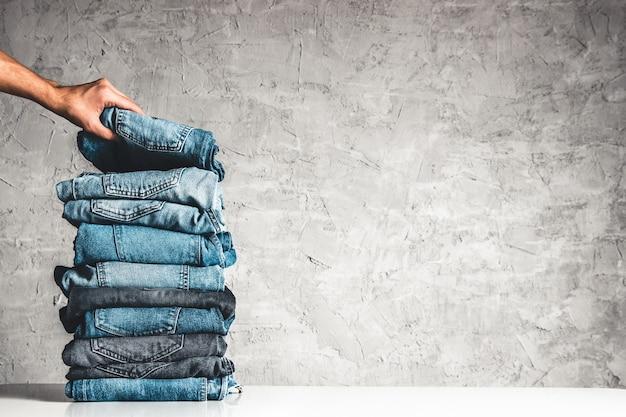 Ręce połóż stos niebieskich dżinsów na szarym tle.