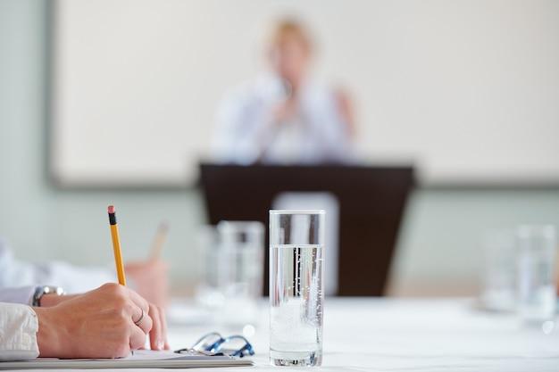 Ręce pracownika medycznego na konferencji, słuchanie badacza i robienie notatek w notatniku