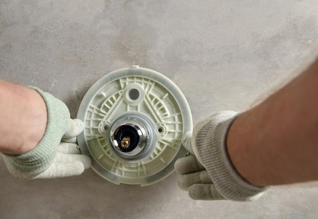 Ręce pracownika montują wbudowany kran