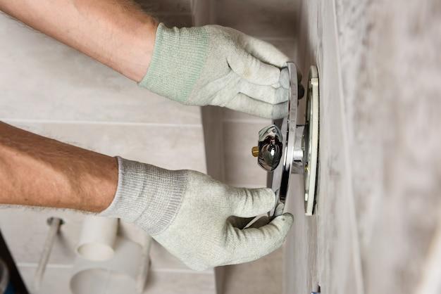 Ręce pracownika montują wbudowany kran.