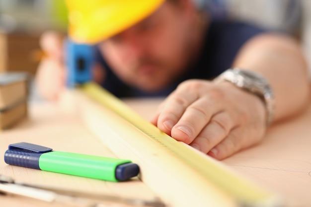 Ręce pracownika pomiaru drewniany bar