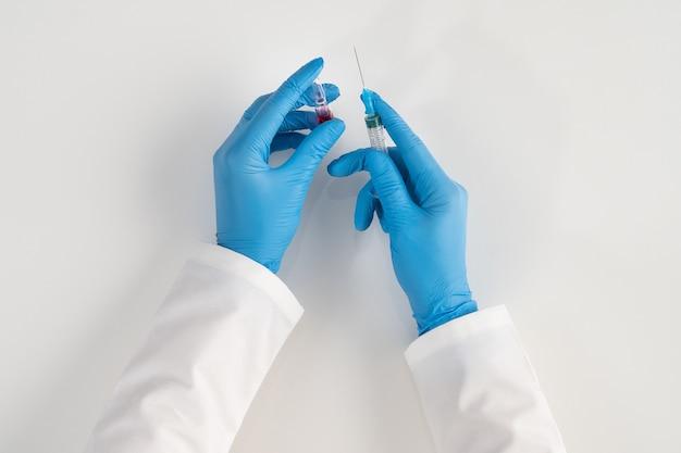 Ręce pracownika służby zdrowia w niebieskich rękawiczkach na białej powierzchni trzymają szklaną ampułkę z czerwonym lekiem i strzykawkę do wstrzykiwań do szczepionek