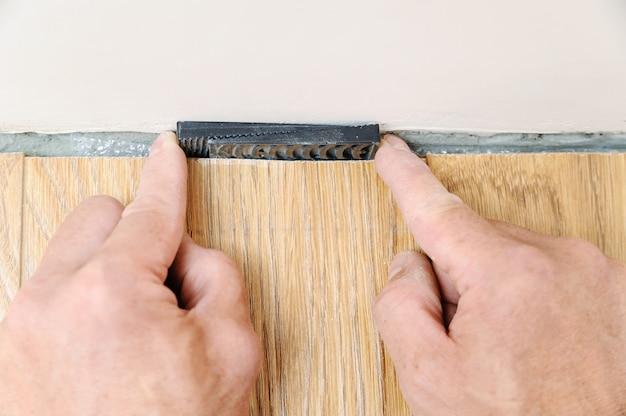 Ręce pracownika umieszczają kliny między ścianą a deską podłogową