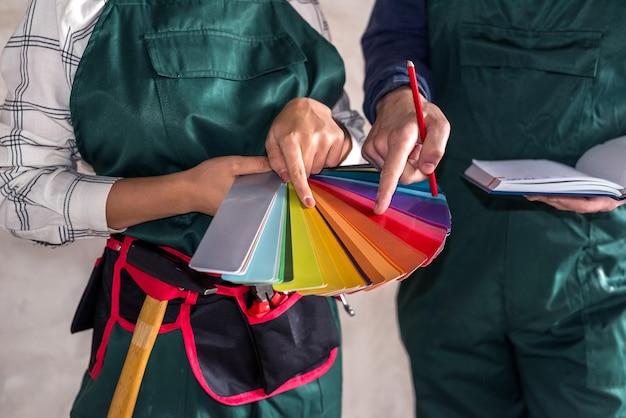 Ręce pracowników wybierające kolor do malowania na próbniku