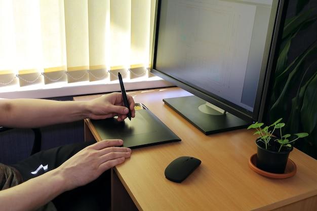Ręce pracują na tablecie graficznym przed monitorem
