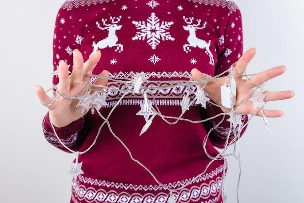 Ręce próbujące rozplątać świąteczne lampki