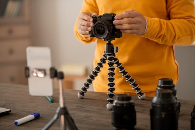 Ręce profesjonalnego fotografa stockowego mocującego aparat fotograficzny na statywie przed smartfonem, robiąc lekcje dla publiczności online