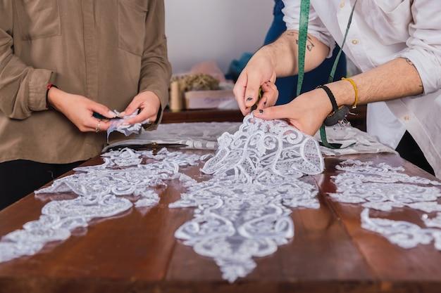 Ręce profesjonalnego krawca pracującego na tkaninach koronkowych ze swoim asystentem w warsztacie.