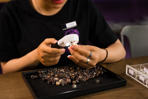 Ręce projektantki biżuterii patrzące na swoją pracę ze szkłem powiększającym