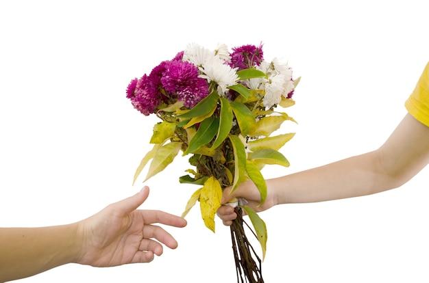 Ręce przekazują bukiet kwiatów na białym tle