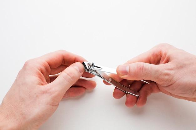 Ręce przycinające własne paznokcie z bliska