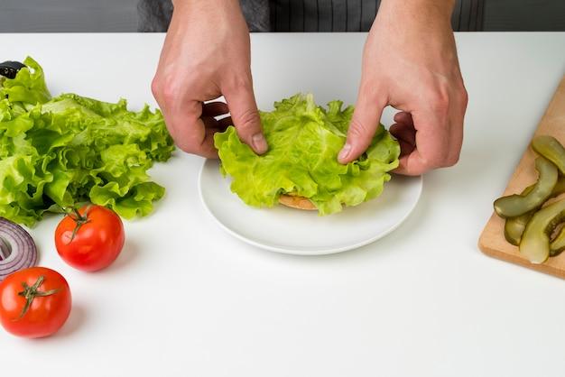 Ręce przygotowuje smacznego burgera