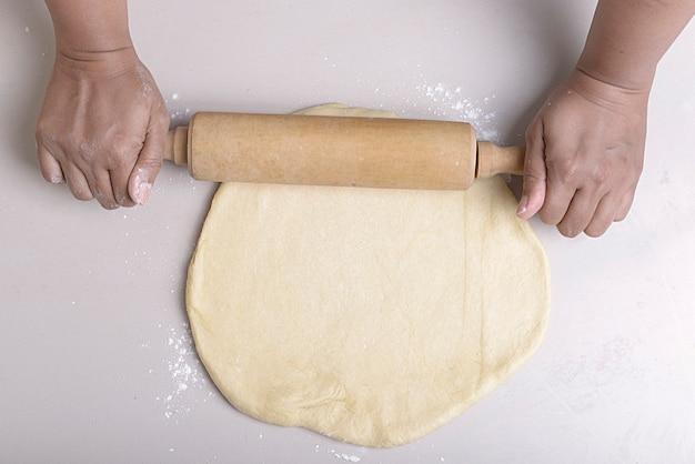 Ręce, robienie ciasta wałkiem na stole