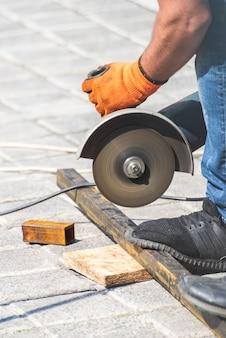 Ręce robocze odcinają metalową rurkę za pomocą szlifierki kątowej