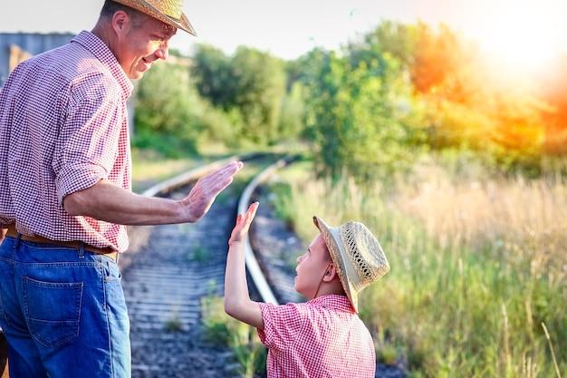 Ręce rodzica i syna w kowbojskim kapeluszu w pobliżu linii kolejowej z walizką