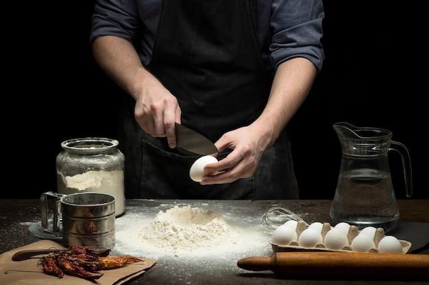 Ręce rozbijają jajko na mąkę, aby zrobić ciasto na drewnianym stole