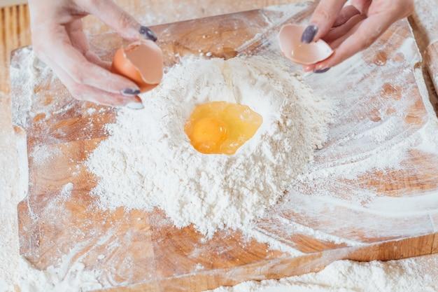 Ręce rozbijające jajo kurze na mąkę na stole