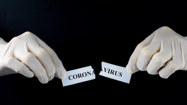 Ręce rozdzierają papier z napisem coronavirus. pandemia covid-19 się skończyła. zatrzymaj rozprzestrzenianie się i wyeliminuj pojęcie koronawirusa. na białym tle na czarnym tle