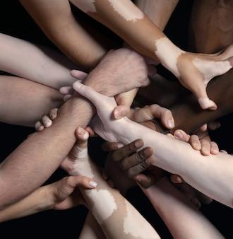 Ręce różnych ludzi w kontakcie na białym tle na tle czarnego studia koncepcja relacji międzyludzkich