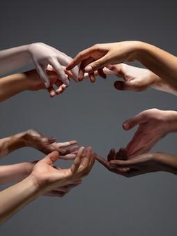 Ręce różnych ludzi w kontakcie na szarym tle studyjnej koncepcji relacji międzyludzkich