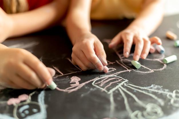 Ręce rysujące kredą z bliska