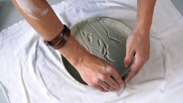 Ręce rzeźbiarza z bliska, które tworzą gliniany talerz