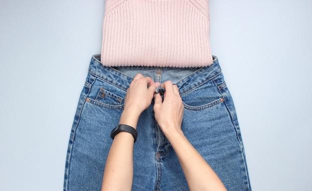 Ręce składają dżinsy na szarym stole. zdjęcie koncepcyjne. widok z góry