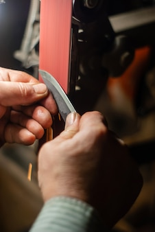 Ręce ślusarza ostrzącego przedmiot do noża na taśmie szlifierskiej