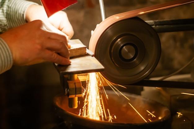Ręce ślusarza szlifującego obrabiany przedmiot na nóż na taśmie szlifierskiej