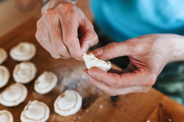 Ręce starszego mężczyzny, gotowania i formowania małe domowe niegotowane pierogi z mięsem na kuchennym stole. narodowa tradycyjna kuchnia rosyjska. zrób to sam. widok z góry