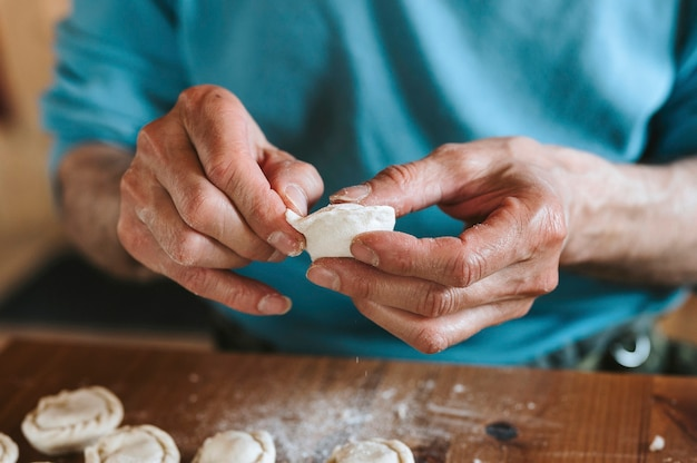 Ręce starszego mężczyzny, gotowania i formowania małe domowe niegotowane pierogi z mięsem na kuchennym stole.