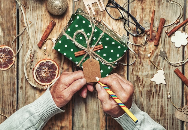 Ręce starszego mężczyzny podpisują prezenty świąteczne na stole z dekoracjami świątecznymi