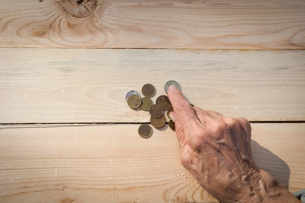 Ręce starszego mężczyzny trzymającego monety. pojęcie braku pieniędzy, biednych, małej emerytury starców. obraz.