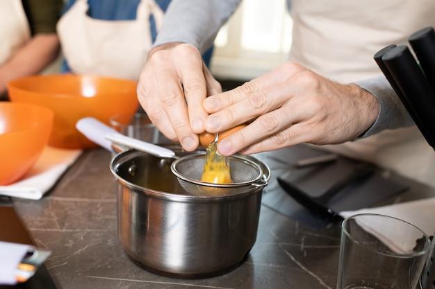 Ręce starszego mężczyzny w fartuchu łamiącym jajko na sito nad metalową patelnią stojącą na stole podczas gotowania czegoś na masterclass w kuchni