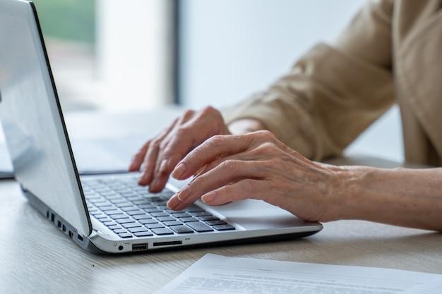 Ręce starszej kobiety na klawiaturze babcia przy laptopie w domu