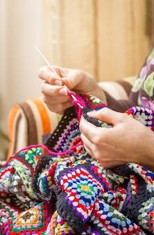Ręce starszej kobiety robiącej na drutach wełnianą kołdrę w stylu vintage z kolorowymi łatami
