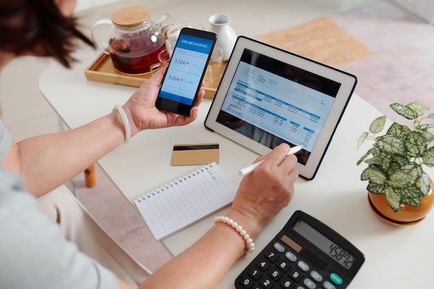 Ręce starszej kobiety sprawdzającej rachunek za media na ekranie komputera typu tablet i płacącej za pomocą aplikacji bankowej na smartfonie