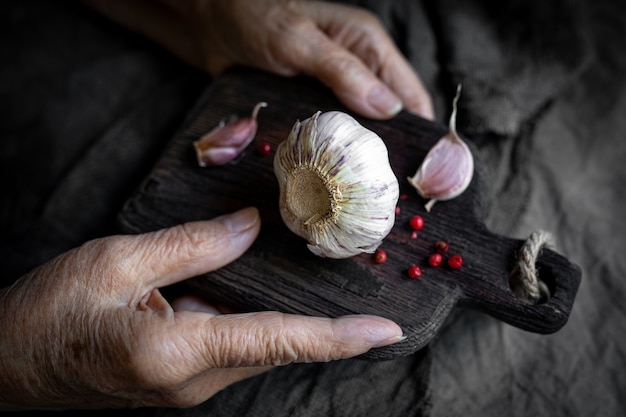 Ręce starszej kobiety trzymają deskę do krojenia z czosnkiem z bliska