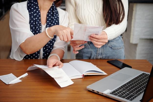 Ręce starszej kobiety wyjaśniającej dorosłej córce, jak płacić rachunki za media online za pośrednictwem strony internetowej na laptopie