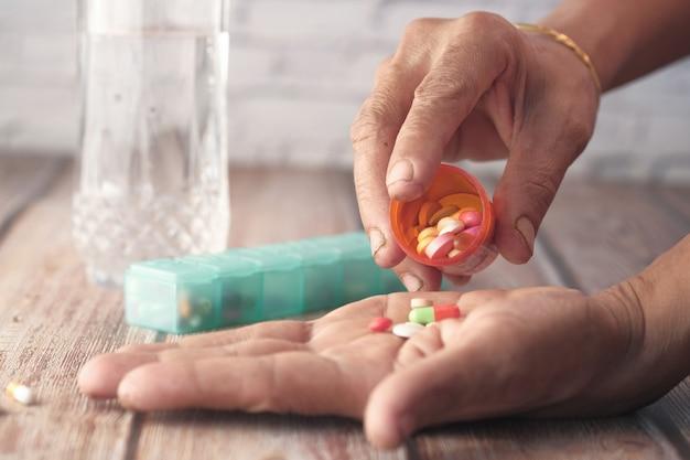 Ręce starszych kobiet biorących leki, z bliska