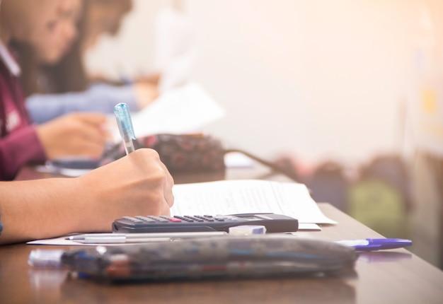 Ręce student uniwersytetu trzyma pióro / kalkulator robi egzamin / studia lub quiz, test od nauczyciela lub w dużej sali wykładowej, studenci w mundurach uczęszczają do szkoły edukacyjnej w klasie egzaminacyjnej.