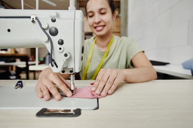 Ręce szczęśliwego młodego krawca pracującego na elektrycznej maszynie do szycia na poduszkach na ramiona dla nowej sukienki, płaszcza lub innego elementu odzieży