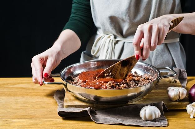 Ręce szefa kuchni dodają koncentrat pomidorowy do mielonej wołowiny
