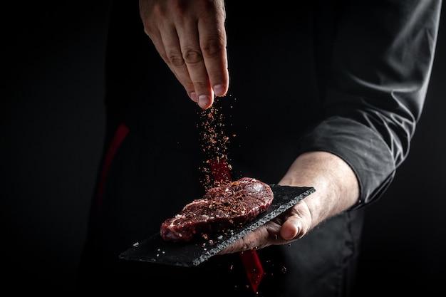 Ręce szefa kuchni gotują stek mięsny i dodają przyprawy w ruchu zamrażania. świeży, surowy stek wołowy prime black angus. baner, przepis na menu.