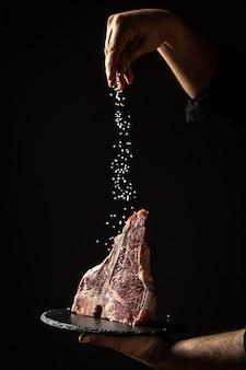 Ręce szefa kuchni gotują stek wołowy wagyu porterhouse na sucho z dużym kawałkiem fileta, dodając sól i pieprz w ruchu zamrażania na czarnej powierzchni