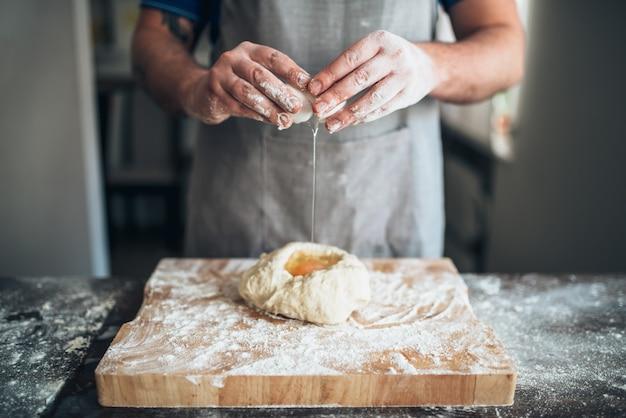 Ręce szefa kuchni mieszają ciasto z jajkiem, przygotowanie chleba