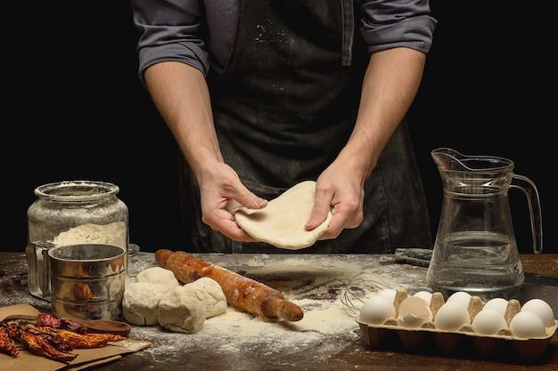 Ręce szefa kuchni przygotowują ciasto na drewnianym stole. niski kluczowy strzał
